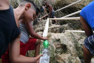 People use tubes to collect water from a mountain on September 28 in San Juan, Puerto Rico